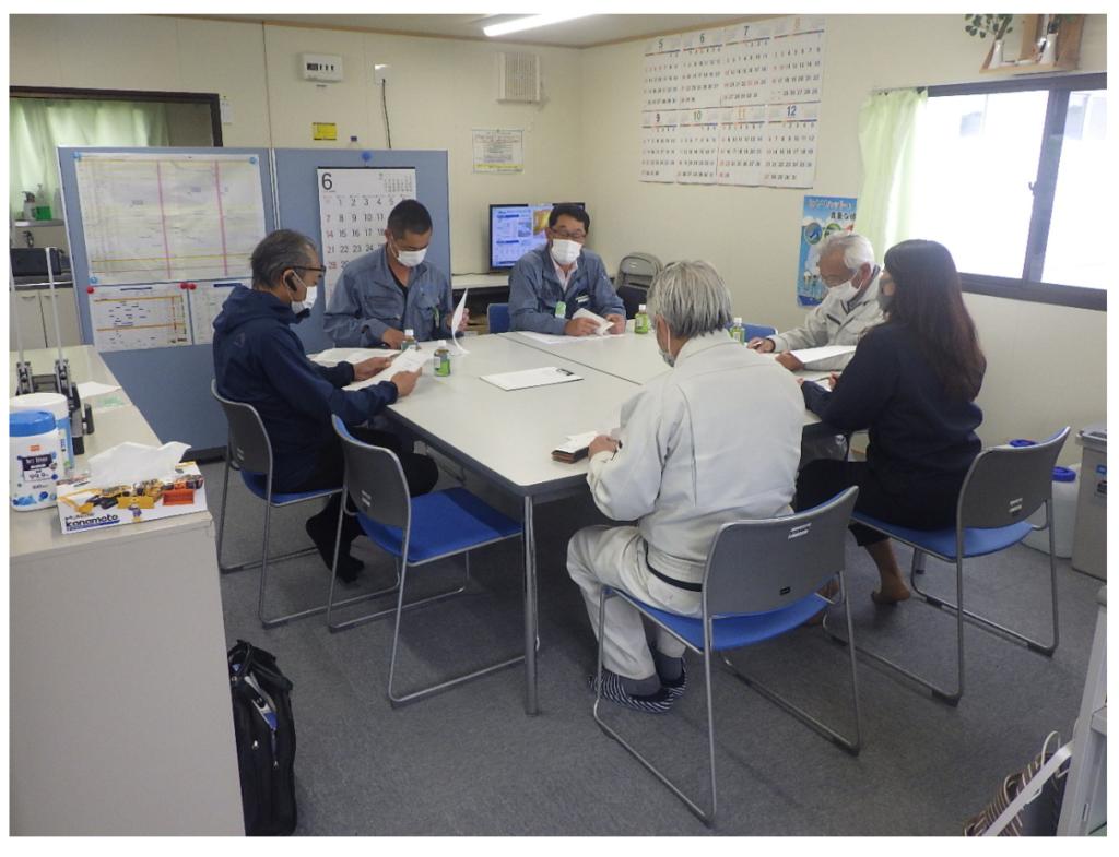 会議室。6人の男女が机を囲んでいる
