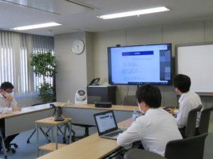 会議室のモニターに映した課題を見る日本コンピュータ開発の社員。