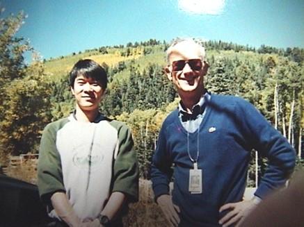 LosAlamos National Laboratory 留学中に撮影された2ショット写真。木々が生える山を背景に、左側でほほ笑む梶村先生。