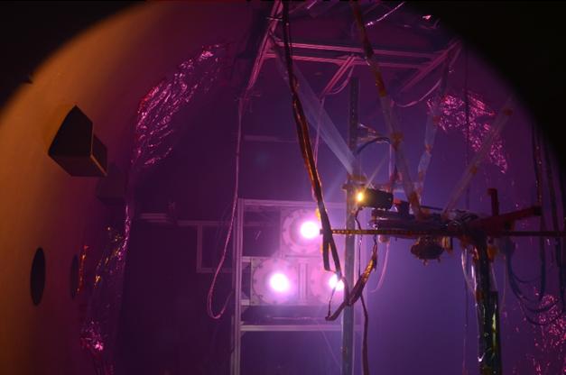 実験風景。中央の同型の3つの機器から紫のライトが発光されている。