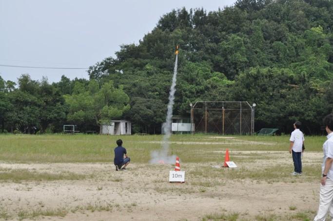 高専スペース連携での活動のようす。広い空き地で上空に向かって飛ぶ小型ロケットの行方を見守る人々。