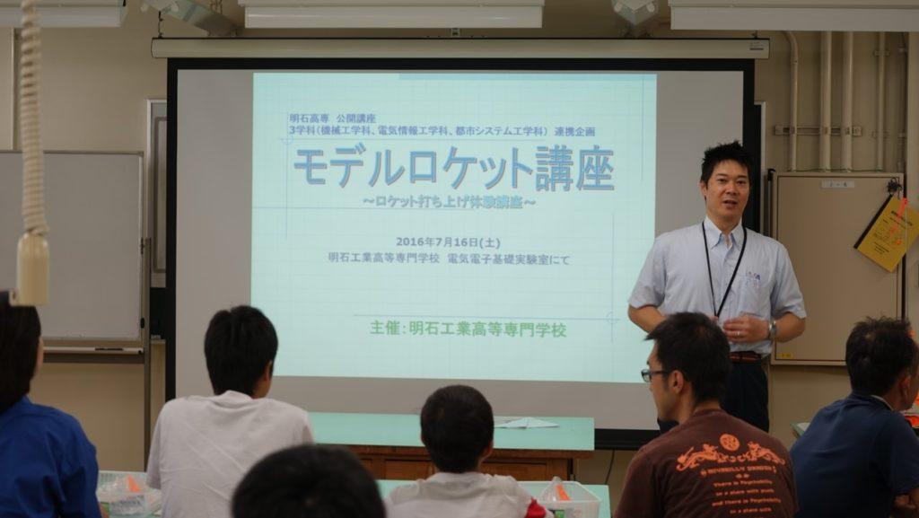 高専生を前に講座を行う梶村先生。 スクリーンには「モデルロケット講座」のスライド。