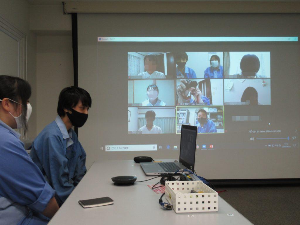 日本ゼオンの会議室。プロジェクターにzoomの画面が映っている