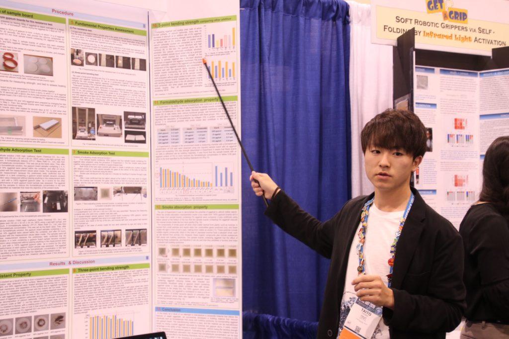 国際大会にて、ブースに展示されたポスターを前に、右手で持ったスティックで場所を指しながら説明する学生の様子。