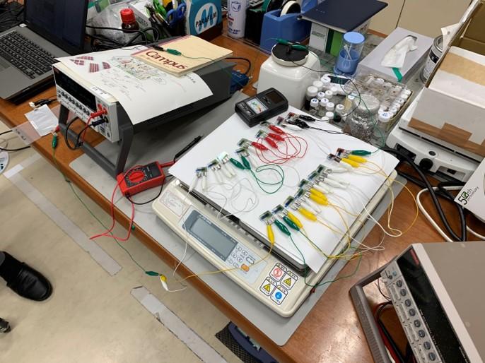 電流電圧を測定する機器。赤や緑、黄色、白、黒などのコードが並ぶ。