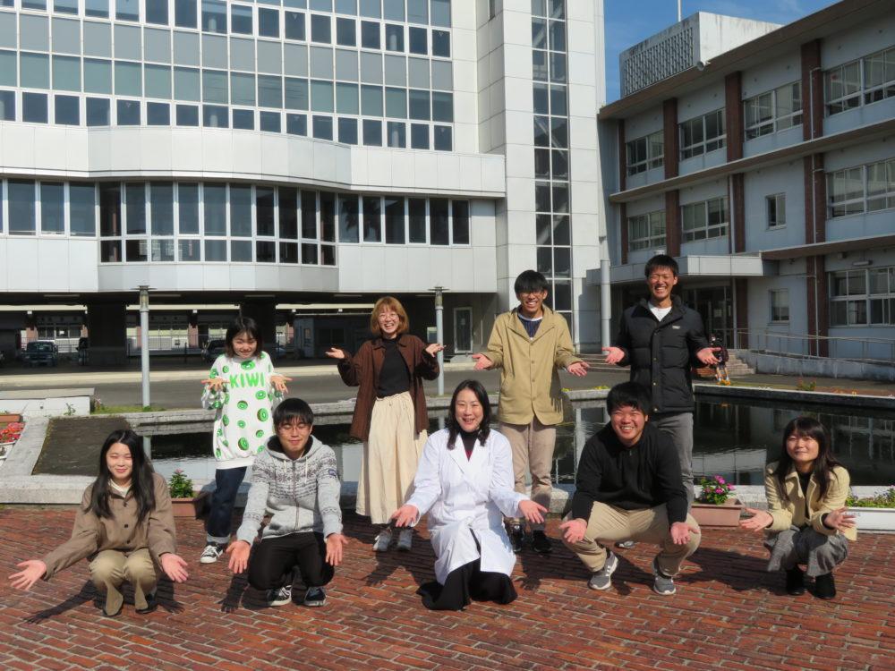 先生を囲む学生8人