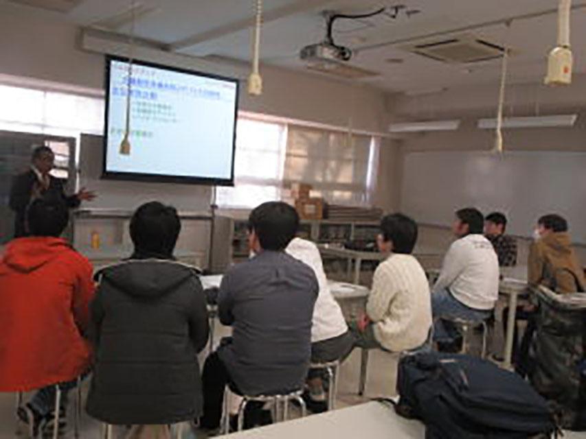小山高専で行われた九工大進学説明会の様子。プロジェクターに映された資料と、前で説明する関係者に、熱心に話を聴く高専生たちの姿。
