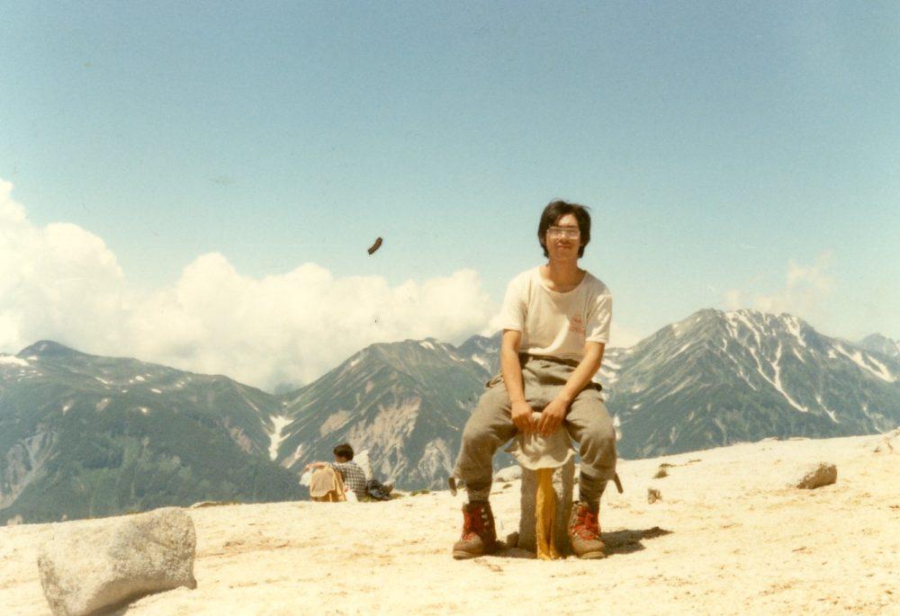 ワンダーフォーゲル部で北アルプスに登った際の写真。半袖長ズボン登山靴で石に腰掛け、山脈と雲と青空を背景に写真におさまる中村先生。