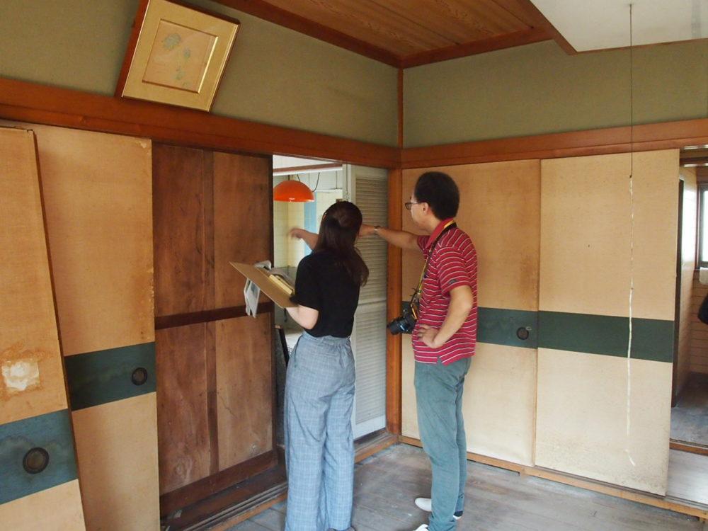 登録があった空き家に、許可を得て、内部調査をしている大島先生と学生。和室だったと想定される、色褪せた障子扉の奥を指さし打合せすする姿。