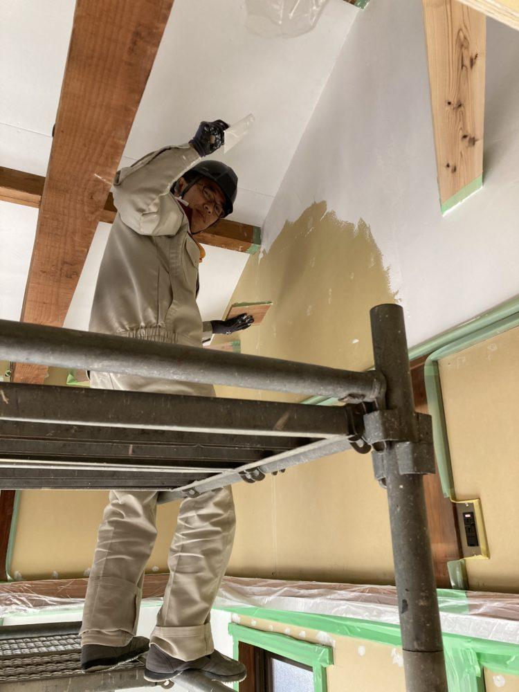 組み立てた足場の上に立ち、造作をする大島先生。作業着にヘルメット姿で、手にはコテを持ち、合板の上から白漆喰を塗っている。