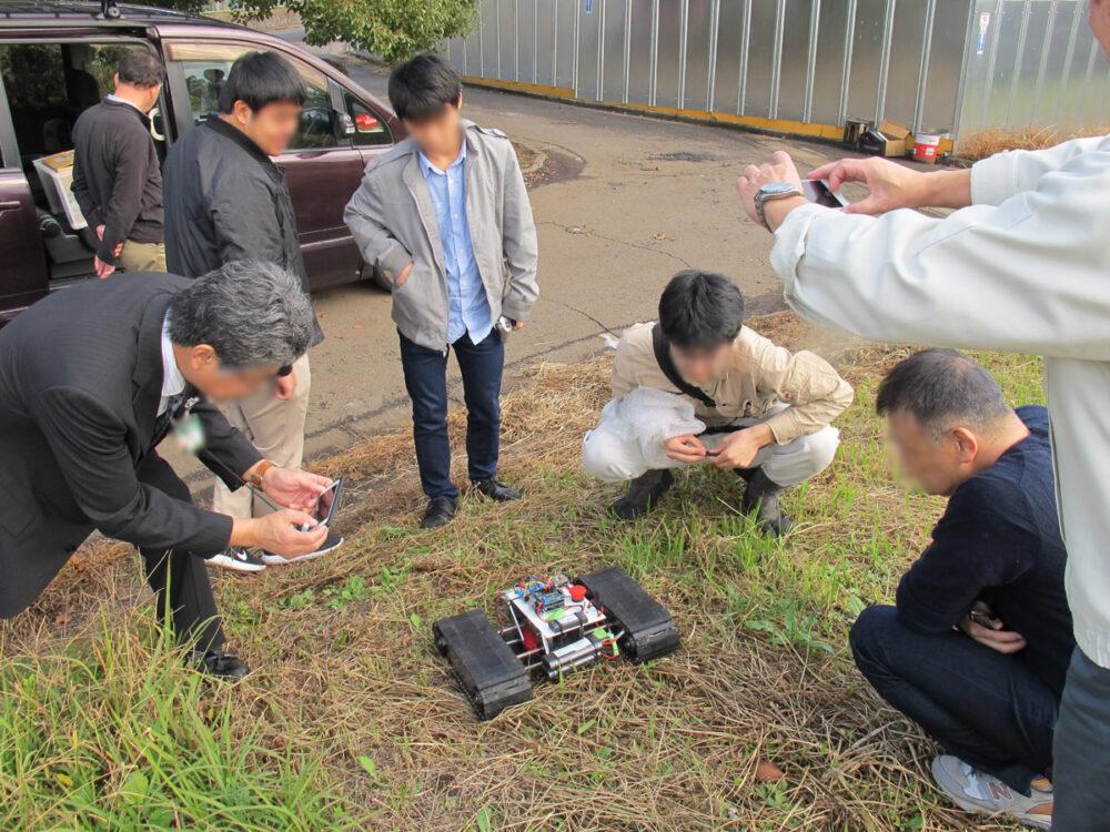 屋外にて、ロボットを囲んで動きを見守る人々。