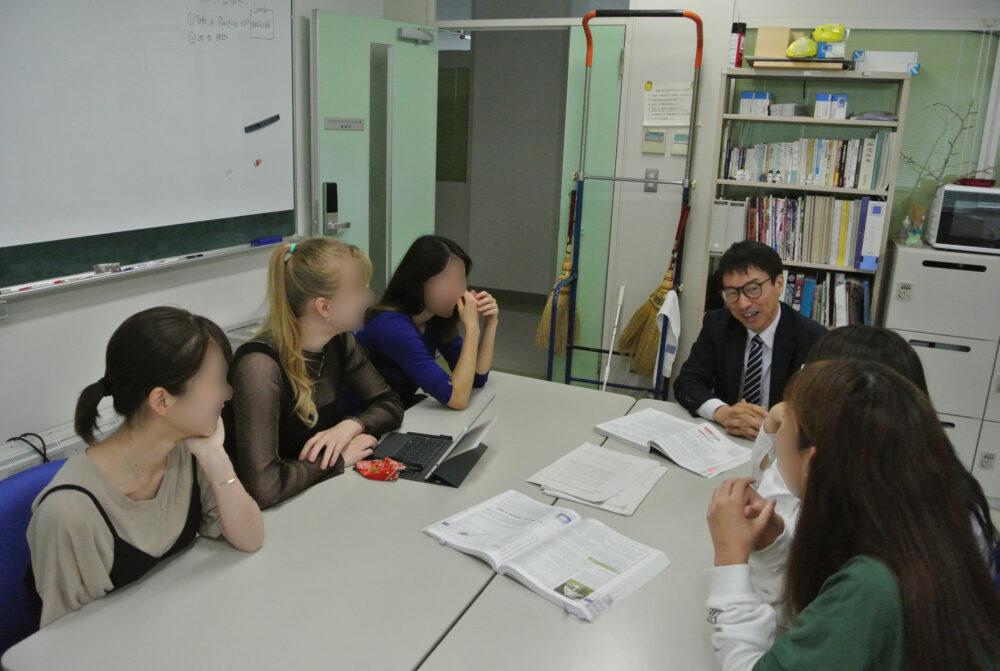 テーブルを囲んで芥川先生と女子学生5名と議論している場面。留学生も。