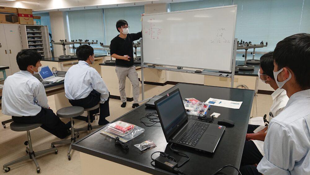 実験室のようなところで。ホワイトボードの横で話す人と、椅子に掛け、前のめりで講義に臨む学生たちの姿。