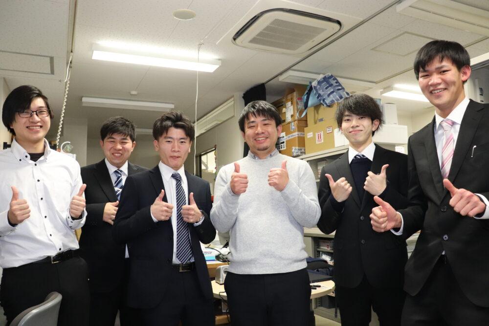 研究室にて。真ん中の猪原先生を囲んで、男子学生5名と。全員で、両手の親指を立てて、グッドポーズ。