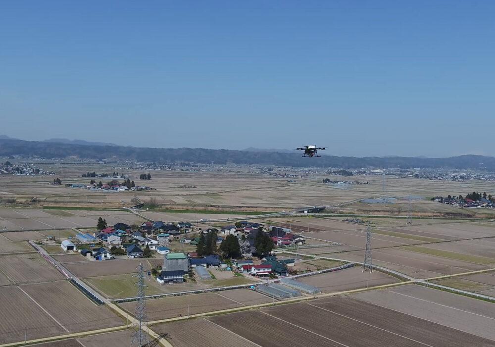 田畑が広がる大地の上空をドローンが飛ぶ。