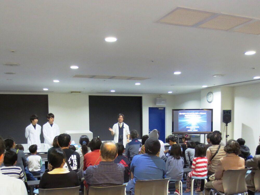 老若男女、受講生を前に化学実験ショーを行う廣木先生。助手の学生さん2名とともに。