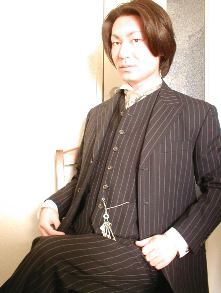 廣木先生(大学生)のポートレート写真。椅子に腰かけ、縦ストライプのジャケットに身を包みポーズをとる。