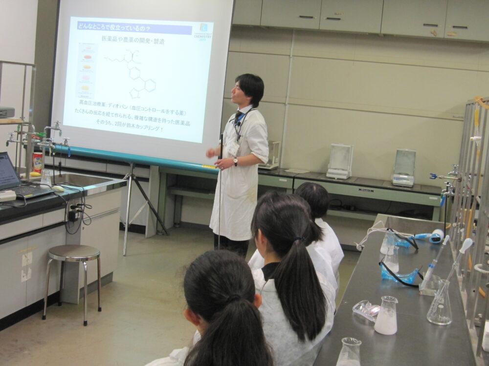 受講生を前に、スクリーンに映したスライドで説明する白衣姿の廣木先生。