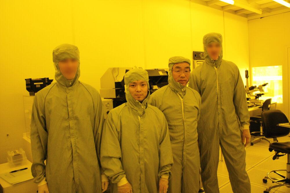 全身防護服に身を包み、現地のかた2名と須田校長とともに写真におさまる柳生先生。背景には機械機器が見える。