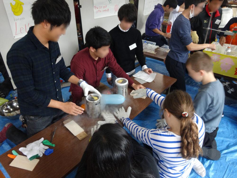 外国の子どもと日本の学生がひとつのテーブルで実験している。真ん中の実験器具からは白い霧のようなものが発生している。