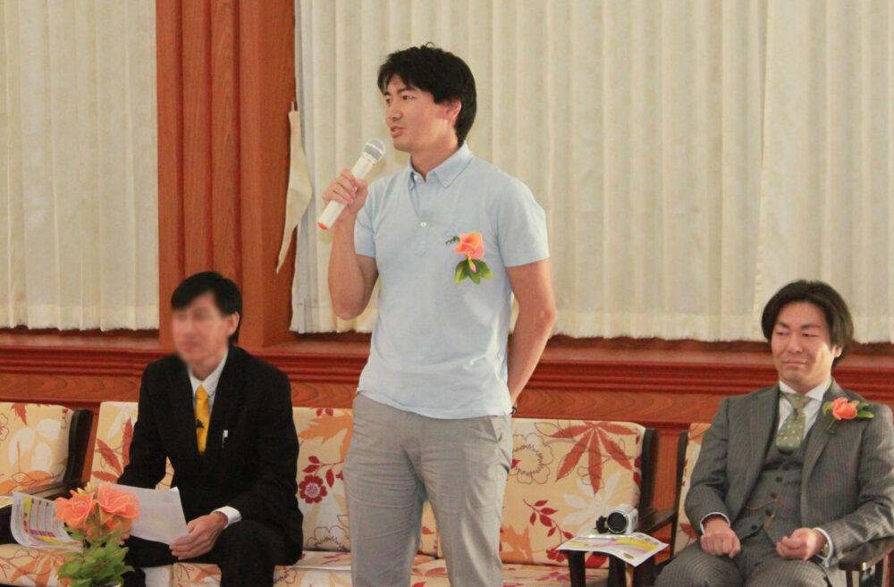 薄い水色のポロシャツに、胸元に華やかなオレンジ色のお花を挿してスピーチをする前澤先生。