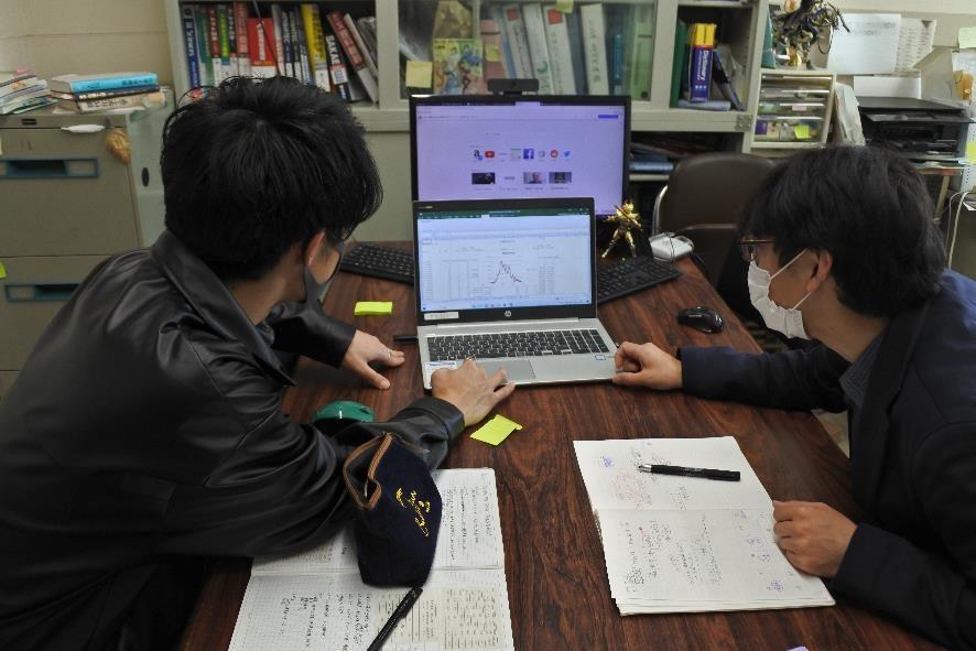 ノートパソコンを間に、左右で学生とディスカッションする様子。