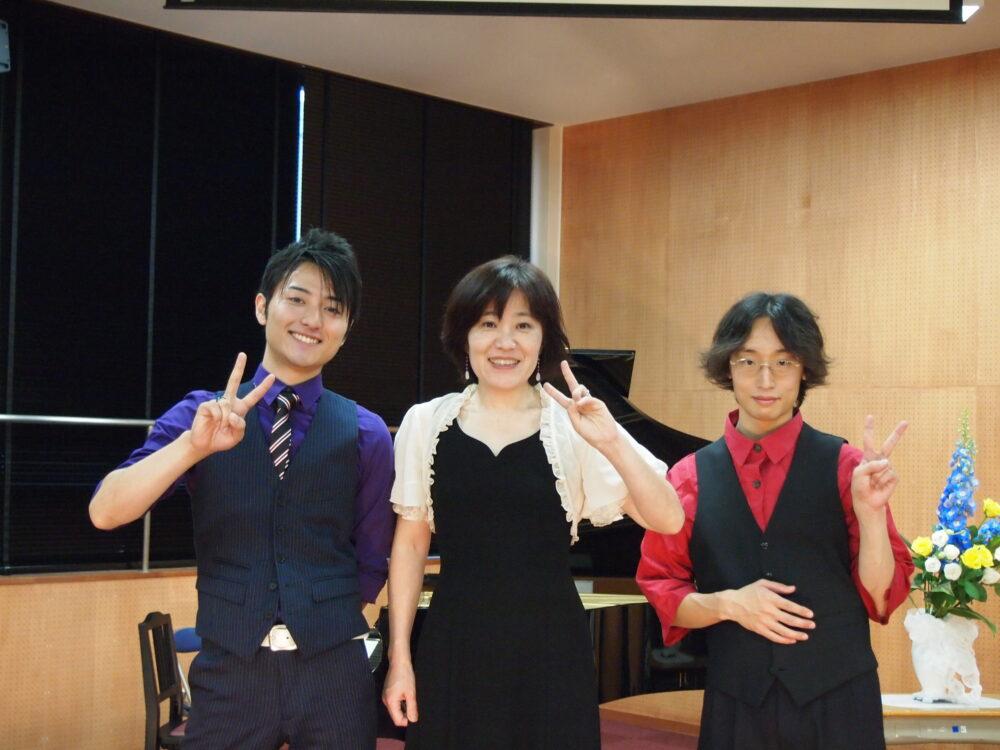 右に赤いシャツに黒のベストを着た、学生時代の工藤先生。コンサートでの計3名でのショット。