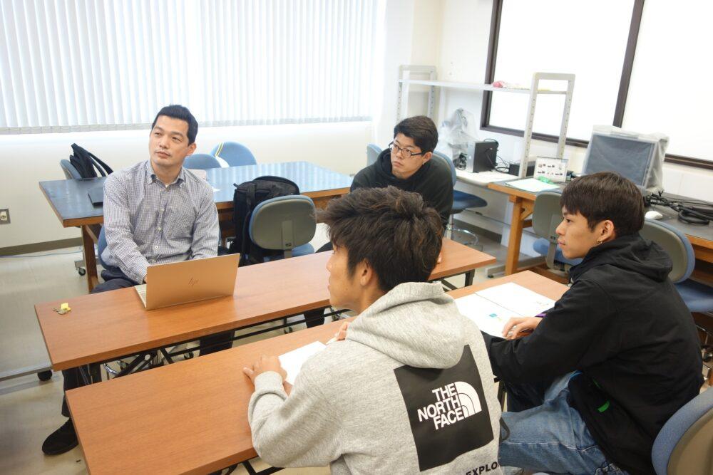 島名先生とその研究室の学生たち。 前方に注目しながら、ミーティングを行っている様子だろう。