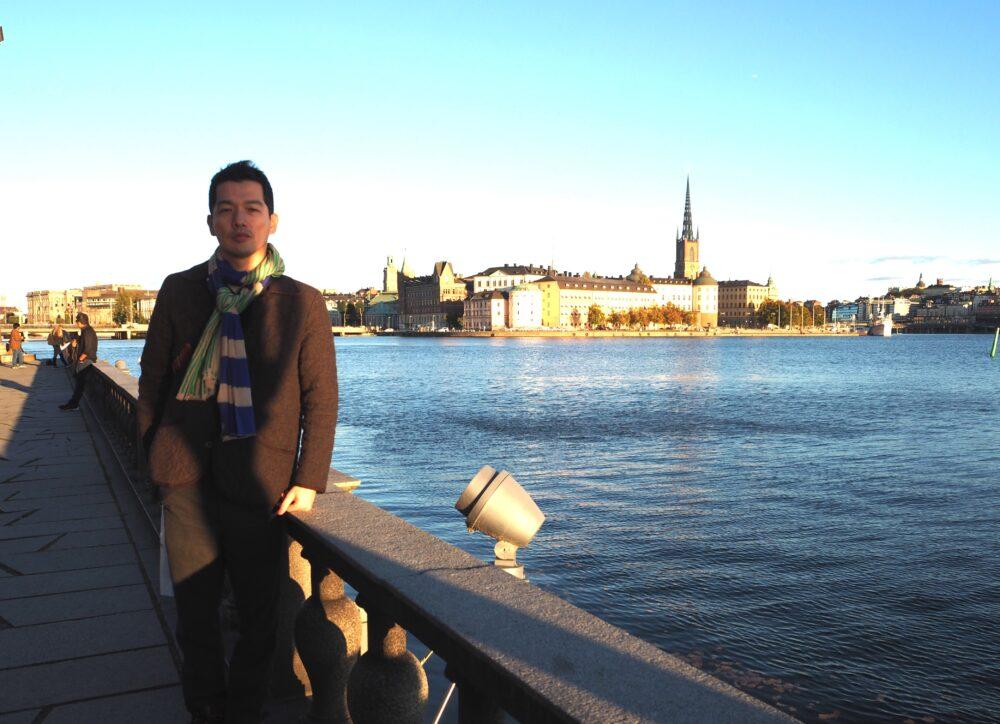 ストックホルムにて。橋のうえで絵になる建築物を背景に、ポーズをとる島名先生。