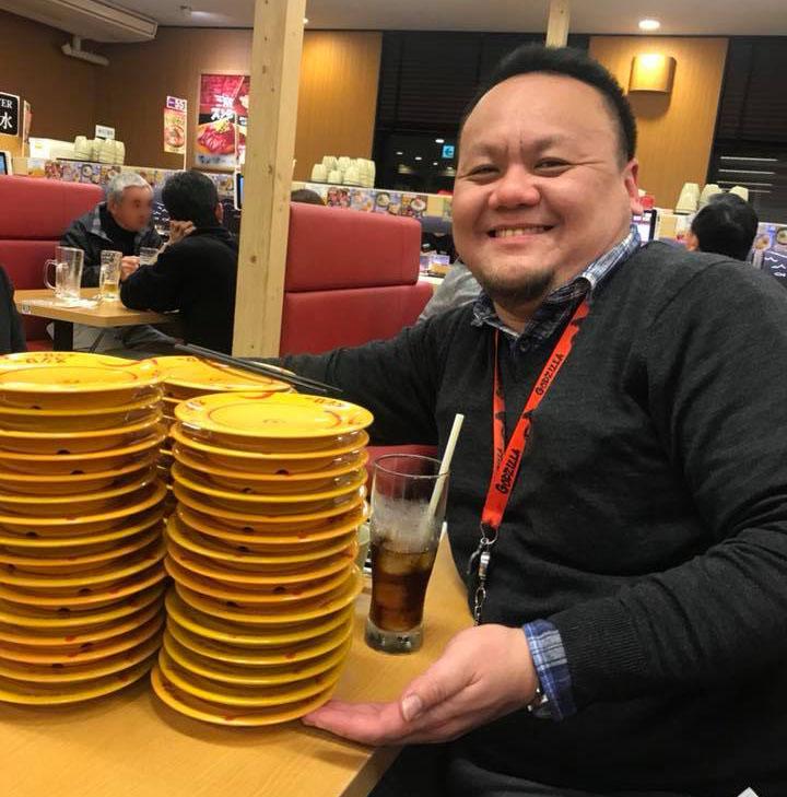 回転すし屋さんにて。20皿×3つほど積まれた寿司皿とともに、笑顔のデフィン先生。