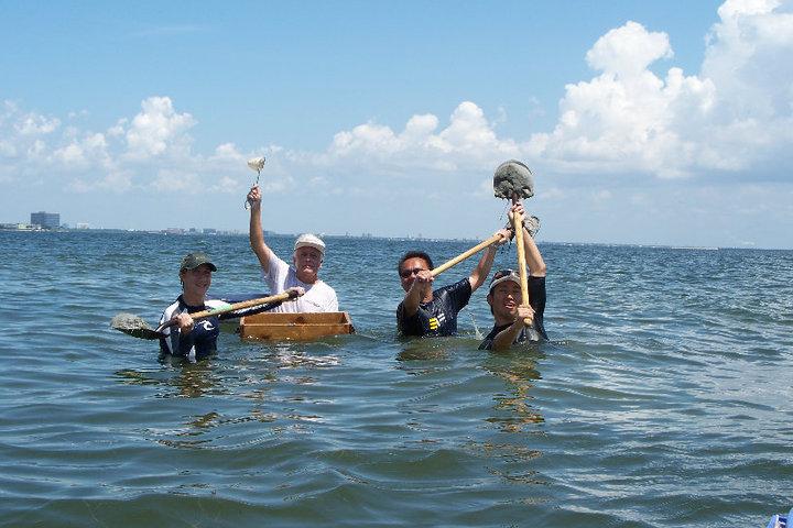 海中から半身だして、採取したサンプルを上に掲げてる。4名で採取。