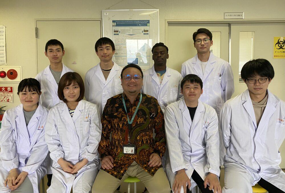 8名の学生と真ん中に笑顔のデフィン先生。 学生はみな白衣を着ている。デフィン先生は印象的な柄のシャツ。