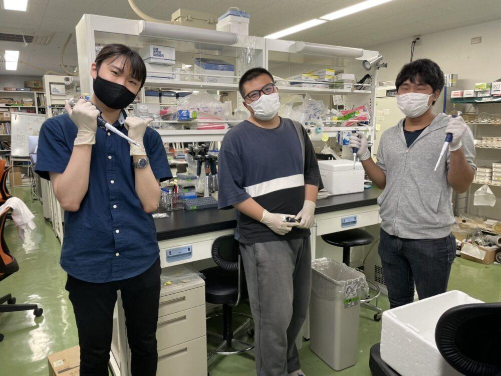 研究室内で、普段実験で使っている器具を手に持ち、写真に応じる3名の院生。