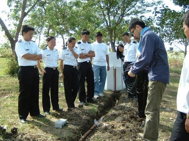 屋外で、制服を着たフィリピン人を教える男性