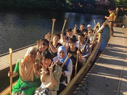 大きな舟を数十人で手漕ぎするアトラクションにて。皆思い思いに笑顔で楽しそうである。