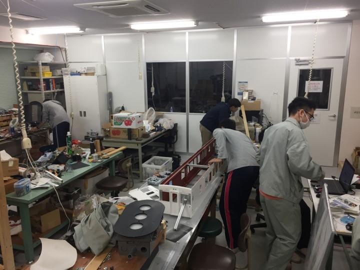 所狭しとものが溢れる部室で、ミニ電車を学生たちがつくっている様子。