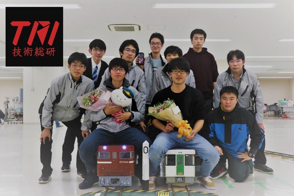 つくったミニ電車にまたがった学生2名ほか、技術総合研究同窓会のメンバーたちと写真におさまる原先生。