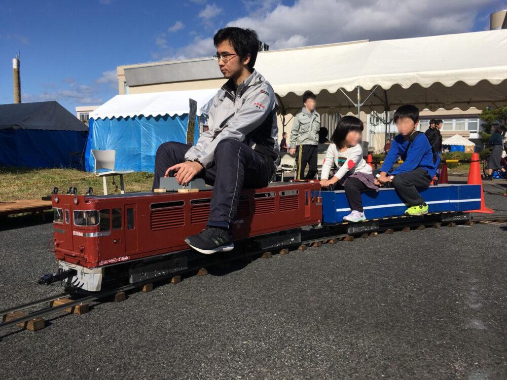 高専祭で、子どもたちを乗せてミニ電車を走らせる学生の姿。