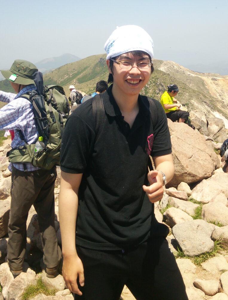 頭にタオルを巻いて、山頂で笑顔の井上先生。