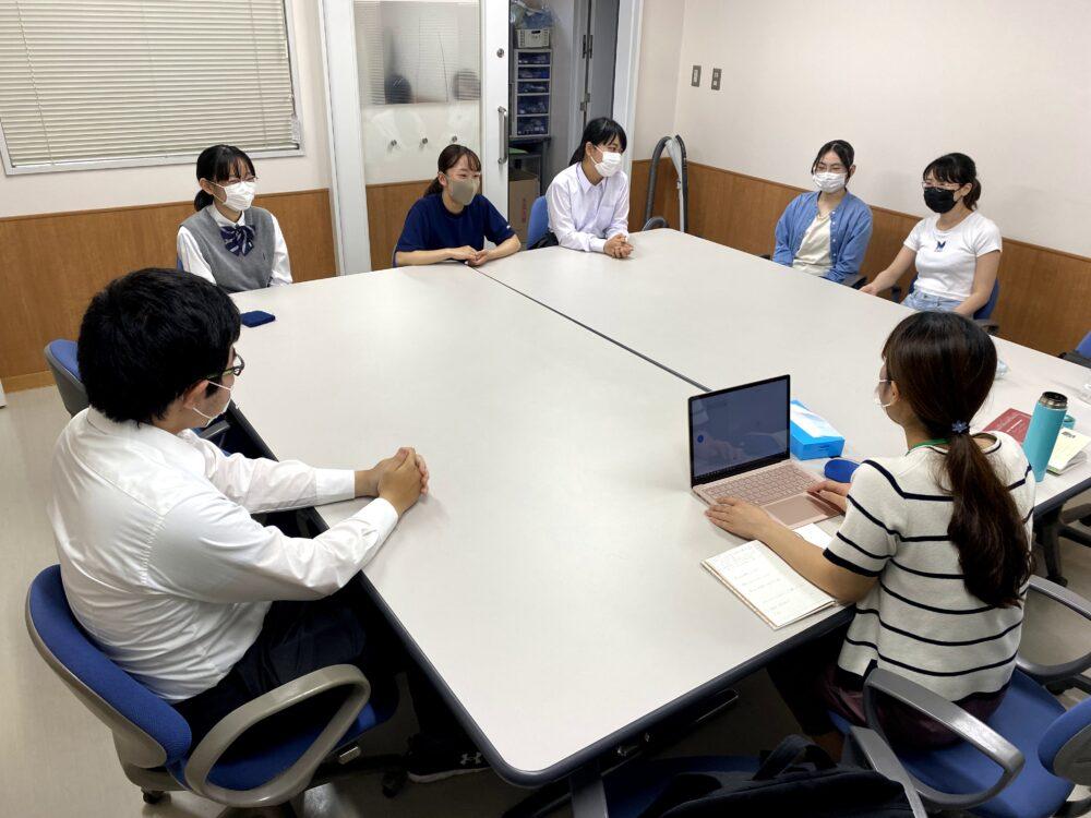 大きなテーブル2つを囲んで、6名の寮生にインタビューしている様子。