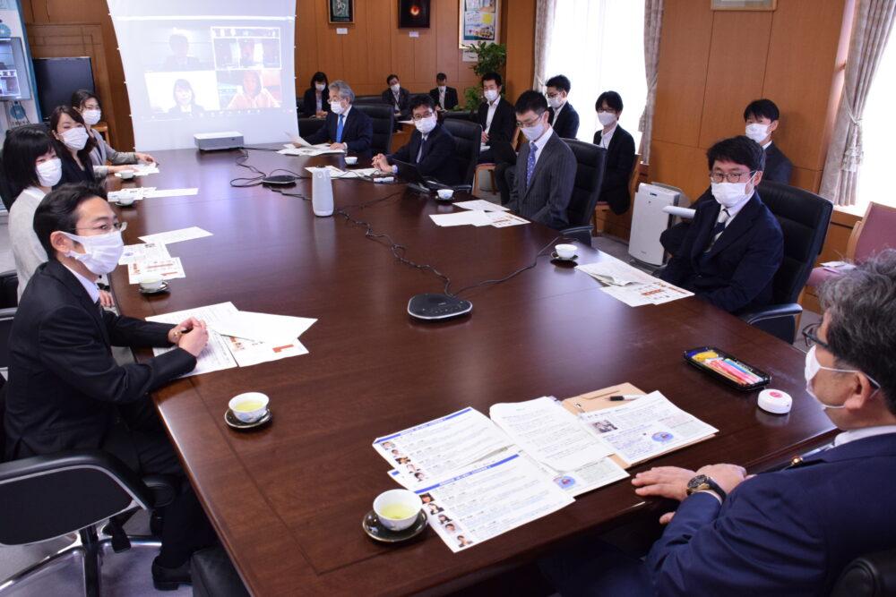 大きな長方形のテーブルを囲むように、当日の参加者と萩生田文科大臣が座って談話する様子。