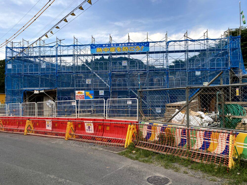 足場が組まれ、工事用フェンスが並んでいる。