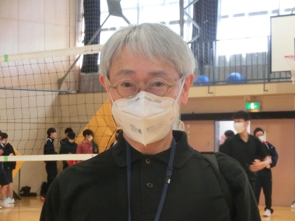 体育館のバレーボールネットを背景に、松江先生の上半身のお写真。