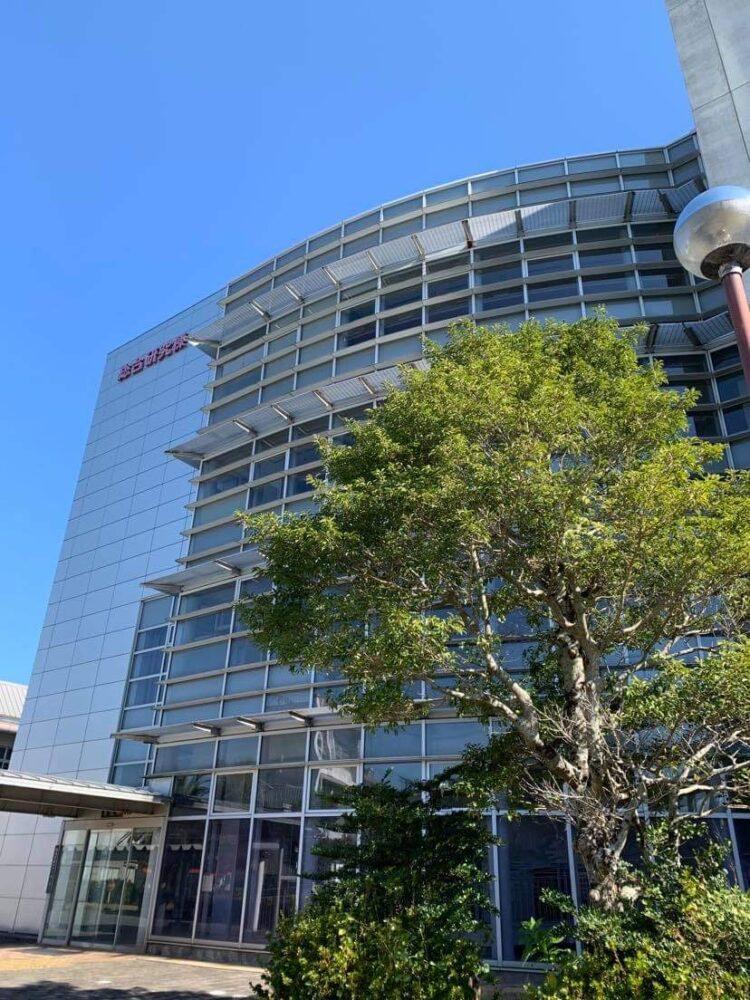 青い空、緑が茂る木、そして銀色に光る外観の4階建ての研究棟外観。