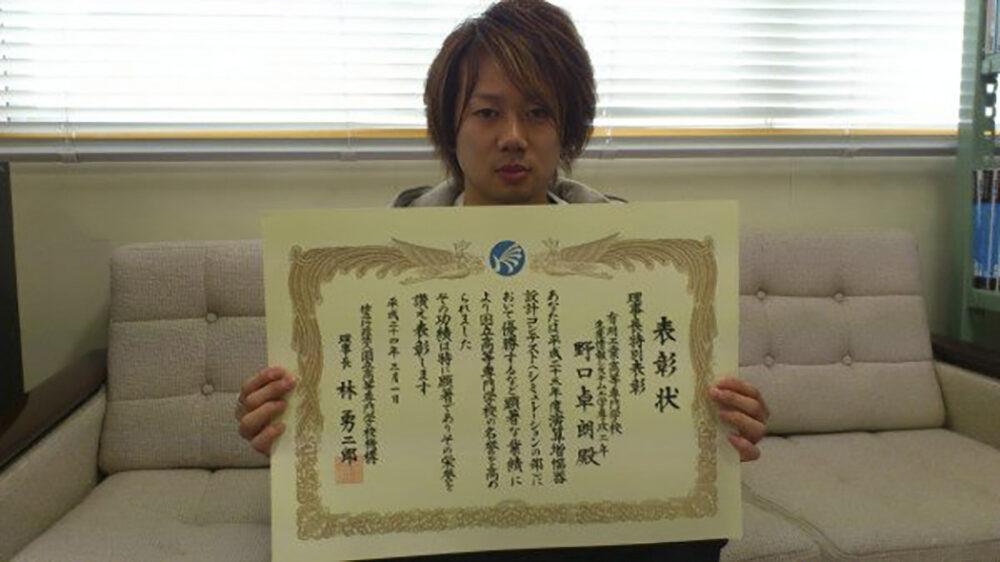 学生時代、表彰状を手にして写真におさまる野口先生。