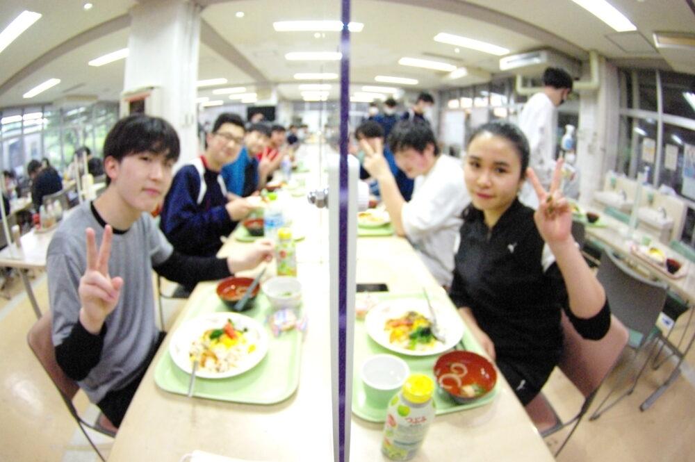 対面式の卓上で、定職を食べている寮生たち。
