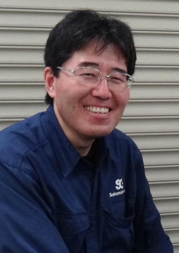 山本さんの上半身の写真。紺色の作業着をきて、柔らかくはにかんでいる。