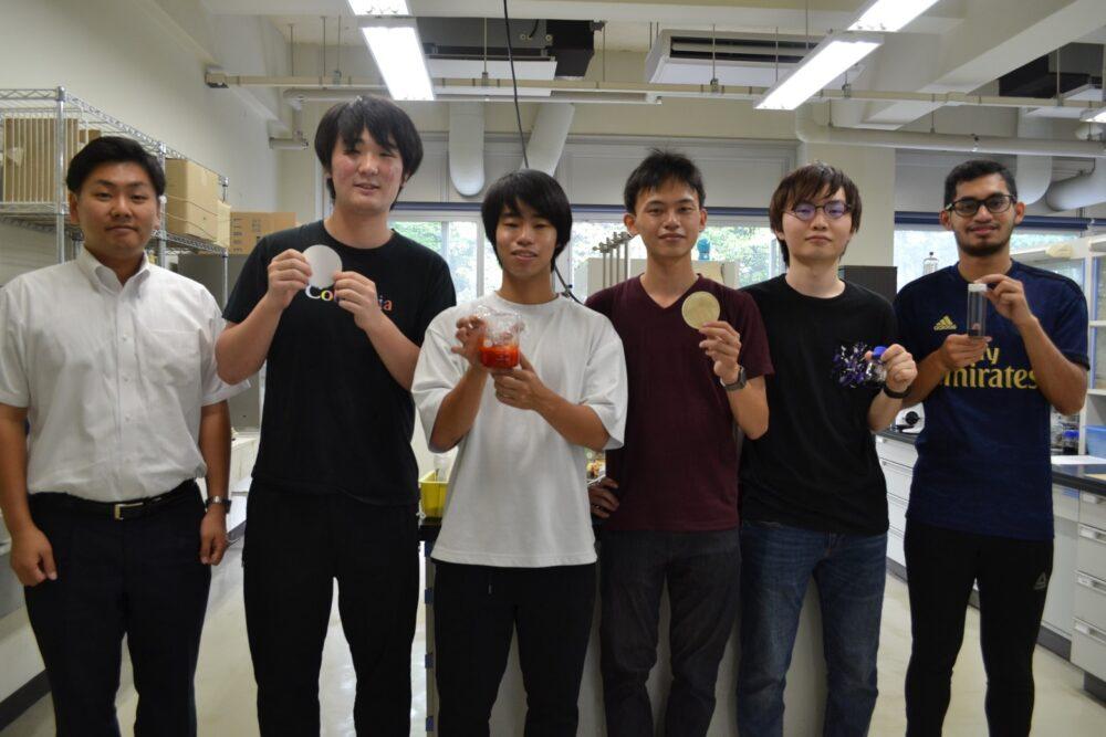 研究室で、学生さんと記念撮影。笑顔の加島先生。