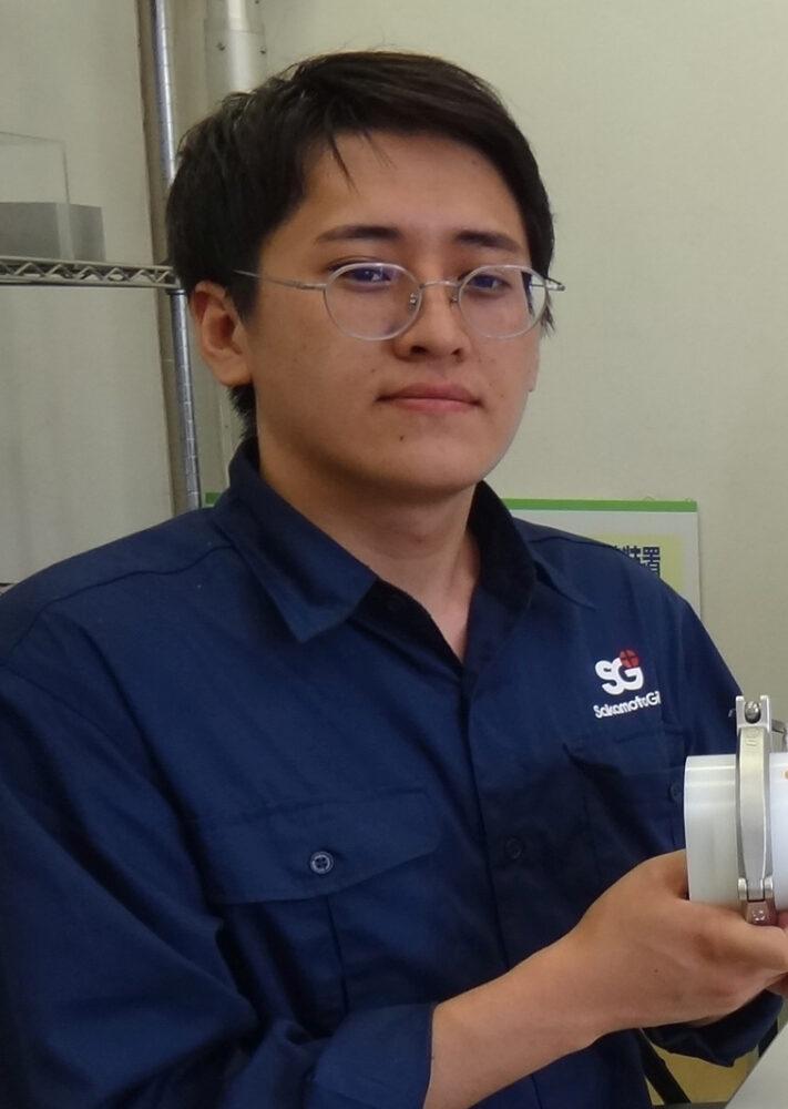 川村さんの上半身の写真。紺色の作業着を着て、緊張した面持ち。