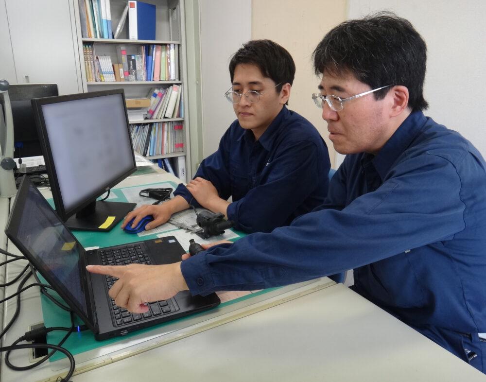 デスクの上で、PCをそれぞれ1台ずつ前に、山本さん、川村さんが打合せしている様子。